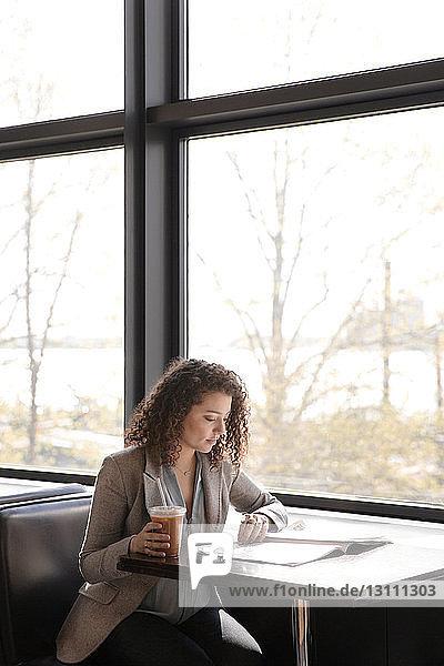 Geschäftsfrau liest Zeitschrift im Café