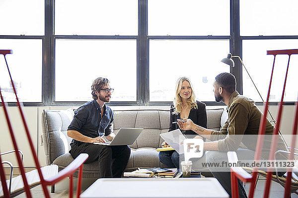 Geschäftsleute  die planen  während sie im Büro am Fenster sitzen