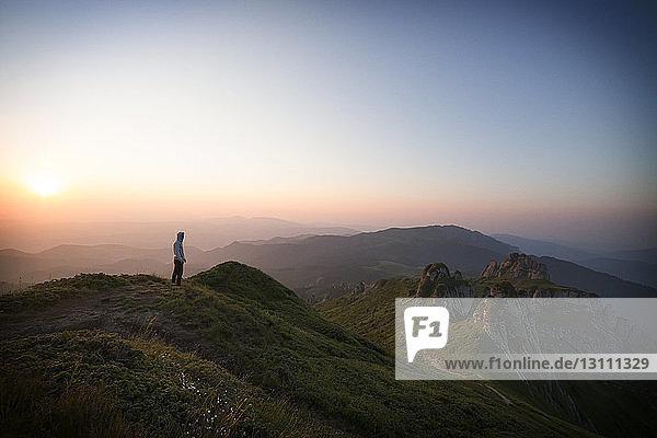 Fernansicht eines Wanderers  der bei Sonnenuntergang auf einem Berg vor klarem Himmel steht