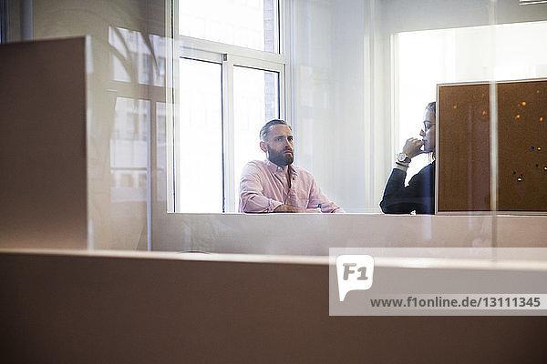 Geschäftsleute  die im Büro planen  durch Glas gesehen