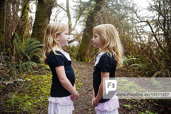 Twin girls standing on field against trees