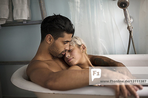 Young couple relaxing in bathtub at home