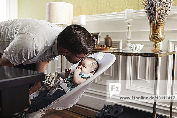 Father kissing daughter sitting on stroller at home