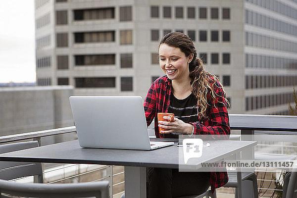 Lächelnde junge Frau benutzt Laptop-Computer  während sie auf der Terrasse eines Cafés sitzt