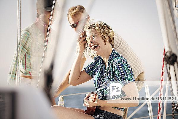 Glückliche Frau genießt mit Freunden auf dem Boot