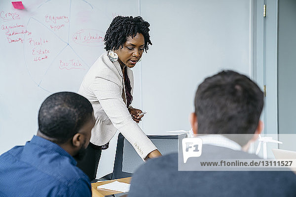 Geschäftsfrau diskutiert im Amt mit männlichen Kollegen