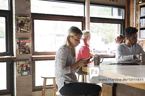 Männliche und weibliche Kunden entspannen sich an sonnigen Tagen im Café