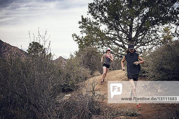 Sportliches Paar läuft am Berg