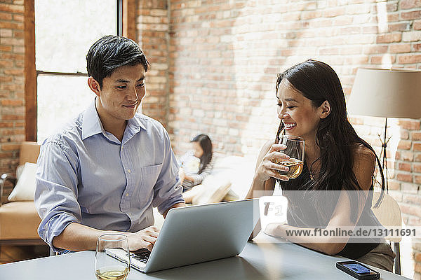 Happy woman with drink looking at husband using laptop computer