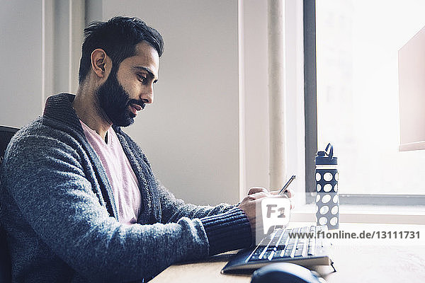 Side view of businessman using smart phone while sitting at desk in office