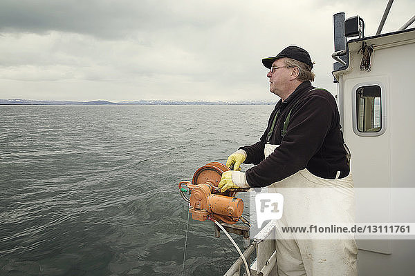 Side view of fisherman standing on fishing boat against cloudy sky