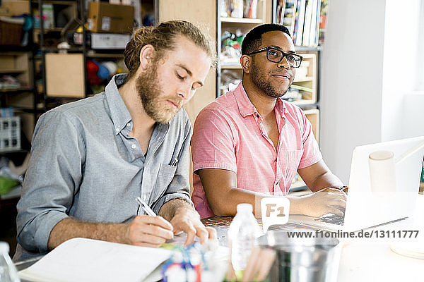 Businessman looking away while male colleague writing at conference table