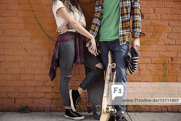 Niedriger Abschnitt des Paares  das sich an der Ziegelmauer stehend an den Händen hält