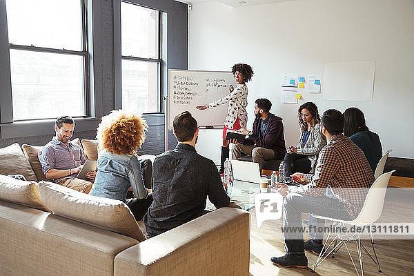 Kollegen betrachten Geschäftsfrau beim Schreiben an der Tafel im Besprechungsraum