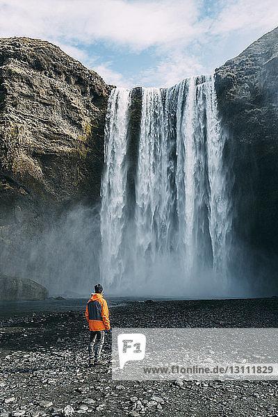 Rückansicht eines Mannes  der den Wasserfall Skogafoss betrachtet