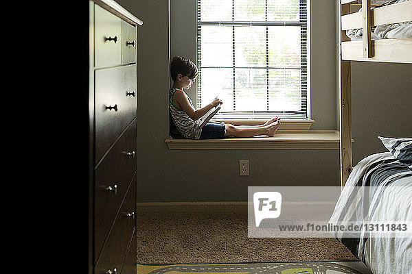 Boy reading book while sitting on window sill