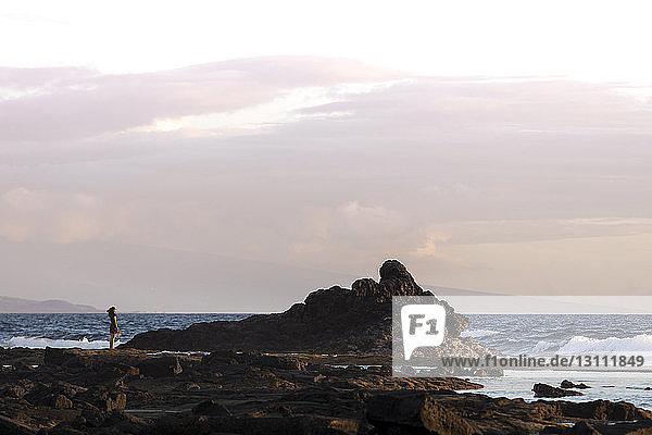 Fernansicht einer Frau  die auf einem Felsen am Meer vor bewölktem Himmel steht