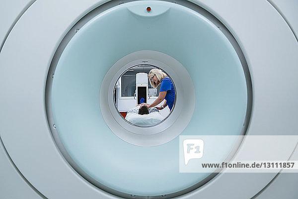 Krankenschwester bereitet Patient für MRT-Scan im Krankenhaus vor  der durch den Scanner gesehen wird