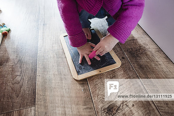 Low section of girl crouching with slate and eraser on hardwood floor