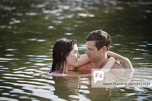 Affectionate couple embracing while standing in lake
