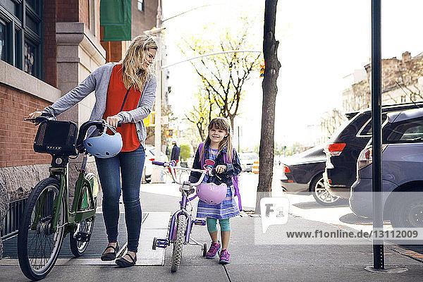 Mutter und Tochter gehen mit Fahrrädern auf dem Bürgersteig