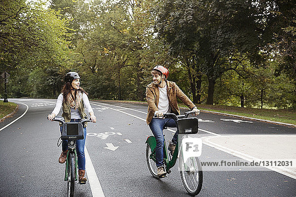Smiling couple riding bicycle on road at park