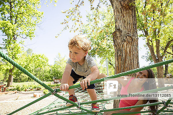 Smiling mother looking at son climbing on ropes in playground