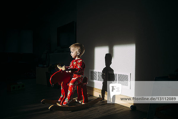 Baby boy looking away while sitting on rocking horse at home