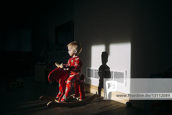 Kleiner Junge schaut weg  während er zu Hause auf einem Schaukelpferd sitzt