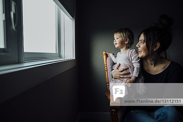 Mother and daughter looking through window while sitting on chair at home