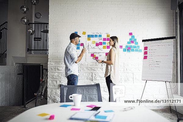 Geschäftsleute diskutieren im Stehen bei Haftnotizen im Kreativbüro