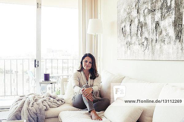 Porträt einer selbstbewussten Frau  die zu Hause auf dem Sofa sitzt