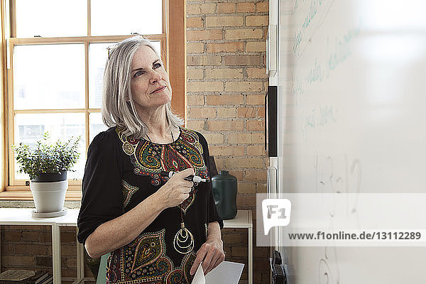 Mature businesswoman analyzing strategy on whiteboard in creative office