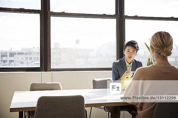 Weibliche Mitarbeiter diskutieren am Schreibtisch im Büro