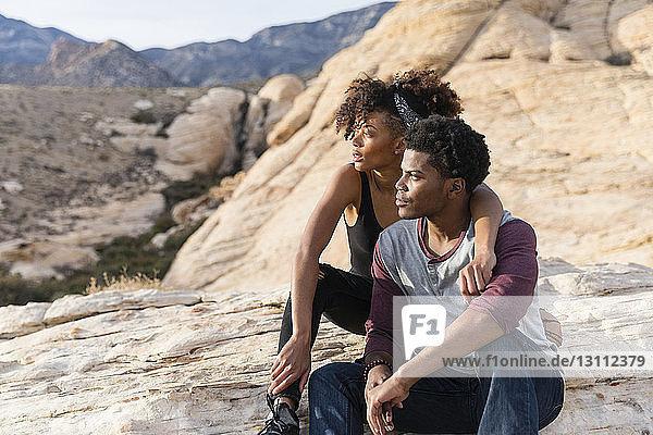 Paar schaut weg  während es auf einer Felsformation sitzt