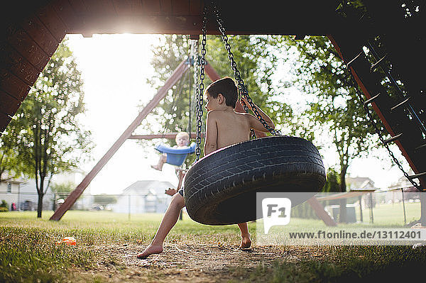 Brothers swinging at playground
