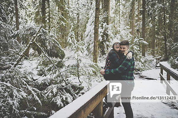 Laughing woman embracing man while sitting on fence in forest at Lynn Canyon Park during winter