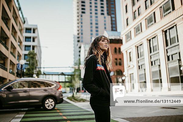Seitenansicht einer jungen Frau mit Händen in den Taschen  die auf der Straße der Stadt steht