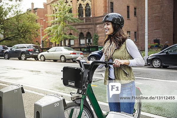 Lächelnde Frau mit Fahrrad schaut weg  während sie auf dem Parkplatz steht