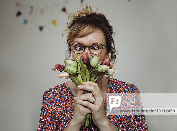 Close-up of woman smelling tulips while making face against wall at home