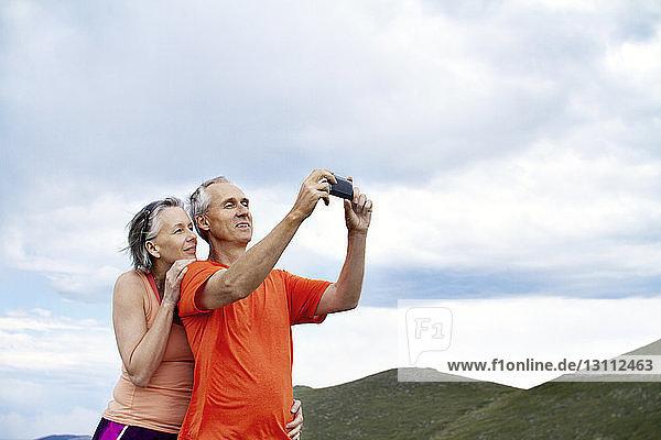 Paarfotografieren mit Smartphone vor bewölktem Himmel