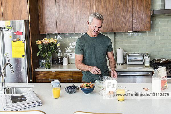 Lächelnder reifer Mann bereitet Essen zu  während er zu Hause in der Küche steht