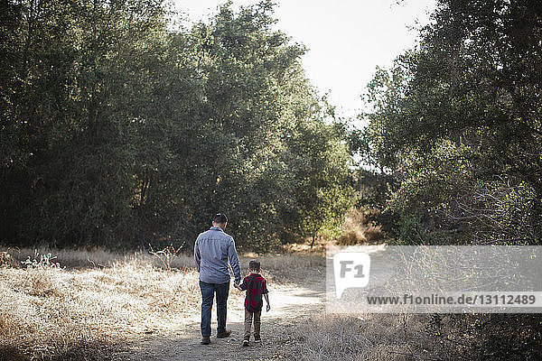 Rear view of father and son holding hands while walking on grassy field
