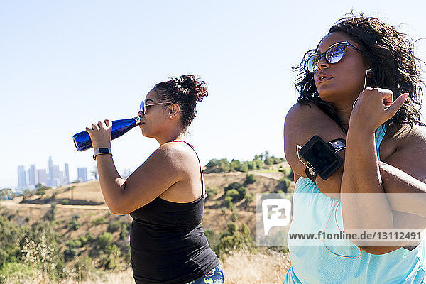 Woman stretching arms while female friend drinking water against clear sky