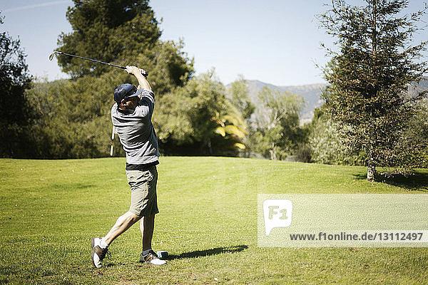 Man swinging golf club on golf course