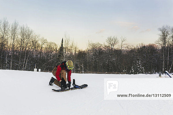 Teenage boy strapping snowboard on snow covered landscape against sky