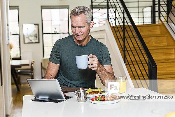 Reifer Mann hält Kaffeetasse  während er einen Tablet-Computer auf dem Esstisch zu Hause benutzt