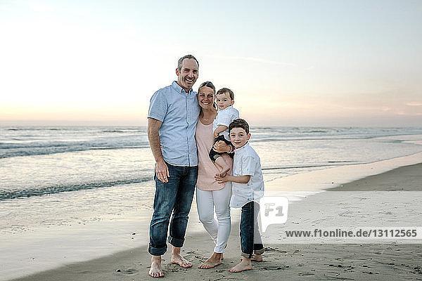 Porträt einer glücklichen Familie  die bei Sonnenuntergang am Strand vor klarem Himmel steht