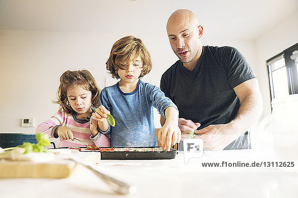 Father preparing food with children at table in home