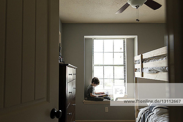 Boy reading book while sitting on window sill at home